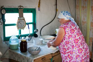 Grandmother prepares dough at its kitchen.