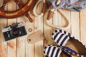 Camera, espadrilles and maritime decorations on the wooden background