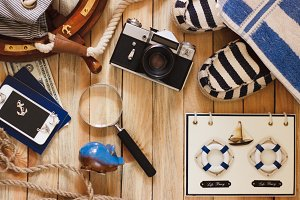 Piggy bank, phone, camera and maritime decorations, wooden background