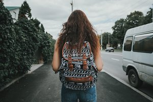 Young student girl walking down the street with a backpack, in the middle of the roadway