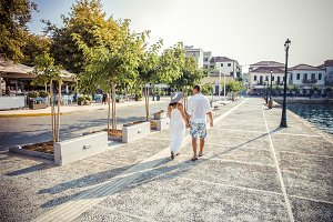 Beautiful stylish pair of summer looks A young lovers couple walks holding hands Girl in a long white dress