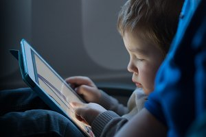 Kid playing with a tablet airplane