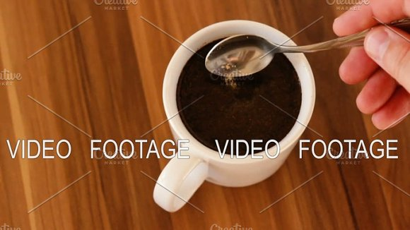 Male Hand Stirring A Cup Of Coffee