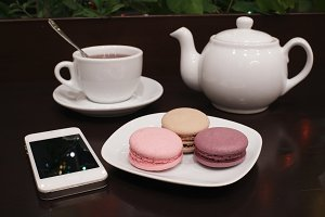 Tea and macaroons with a tablet