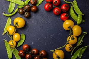 Food cooking background with red and yellow tomatoes and green pea. Copy space, top view