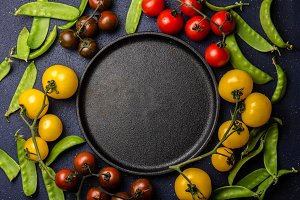 Food background with copy space. Red and yellow tomatoes and green pea around epty black cast iron plate. Top view
