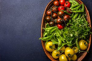 Red and yellow tomatoes, watercress salad and green pea on try. Harvest or clean healthy eating concept. Top view.