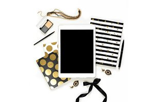 Flat lay fashion feminine home office workspace with tablet, stylish black gold notebooks, cosmetics and jewelry on white background. Top view on women's business work desk