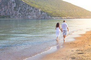 Young happy couple walking on seashore