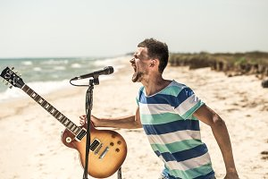 rock on the beach, the musician plays the guitar and sings into the microphone, the concept of leisure and creativity