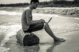 man working with computer on the beach