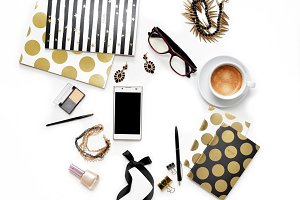 Flat lay fashion feminine home office workspace with phone, cup of coffee, stylish black gold notebooks, cosmetics and jewelry on white background. Top view on women's business work desk