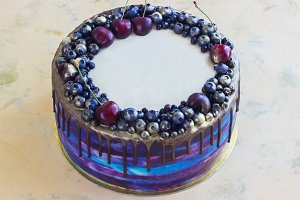 Bright festive blue cake with berries and chocolate