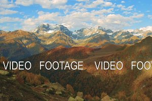 Golden autumn mountain hills, snow tops and red forest. cloud shadows show relief. timelapse