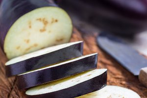 Preparing vegetable dish. Eggplant and eggplant slices on a wooden cutting board and background, vertical