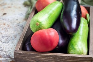 Ingredients for ratatouille or vegetable dish: eggplants, zucchini and tomato in a wooden box, horizontal, copy space