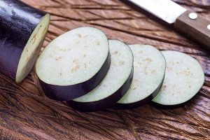 Eggplant and eggplant slices on wooden cutting board, horizontal