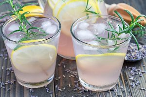 Homemade lemonade with lavender, fresh lemons and rosemary on wooden table, horizontal