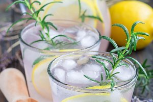 Homemade lemonade with lavender, fresh lemons and rosemary on wooden table, vertical