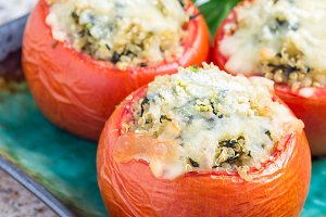 Baked tomatoes stuffed with quinoa and spinach topped with melted cheese on the plate, vertical, copy space