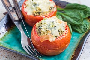 Homemade baked tomatoes stuffed with quinoa and spinach topped with melted cheese on the plate, horizontal