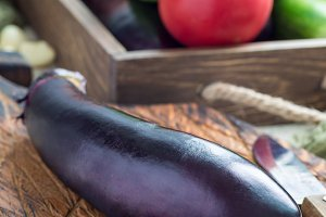 Preparing vegetable dish. Eggplant on a wooden cutting board, vegetables on background, vertical