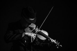 Violin player in dark studio