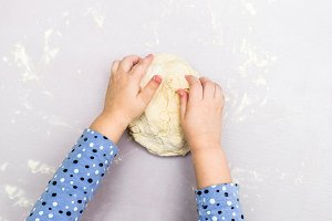 Children hands make a dough