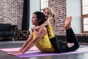 Young Caucasian mother doing yoga cobra pose on floor while her smiling daughter sitting on moms back hugging her in living room