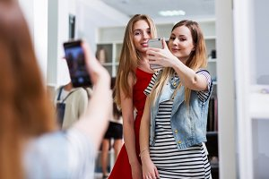 Two smiling girls taking selfie while shopping in a clothing store