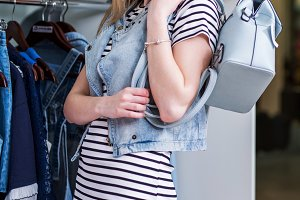 Young smiling female model posing in a showroom in stylish casual summer outfit with a backpack