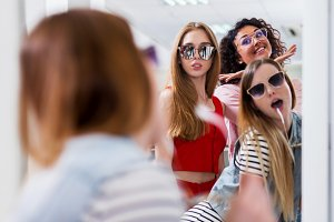 Trendy female friends trying on stylish sunglasses looking in mirror, smiling, having fun in accessory store