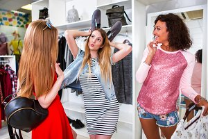 Group of girlfriends spending time together having fun doing shopping. Pretty girl showing ears with shoes in fashion store