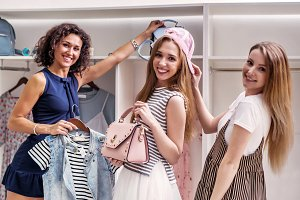 Happy funny female friends picking new clothes and accessories looking at camera in boutique
