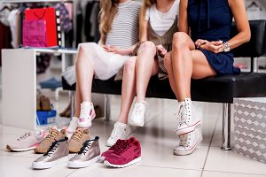 Girls choosing teen shoes surrounded by youth footwear at trendy clothing shop