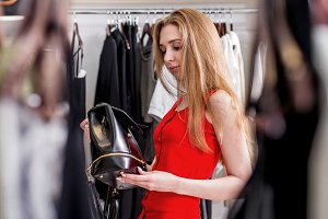 Caucasian young female shopper choosing leather backpack from new women s collection