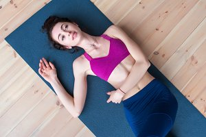 Pretty smiling Caucasian girl lying on floor relaxing at the end of yoga class
