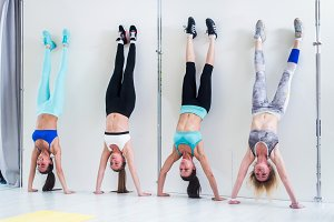 Fit girls doing handstand against wall indoors