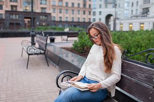 Young beautiful girl with glasses long brown hair sitting on a bench with a book. She left the house on a warm evening to read in the yard. The urban background