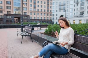A beautiful young girl with long brown hair sitting on a bench with a book, holding eyeglasses. She left the house on a warm evening to read in the yard. The urban background