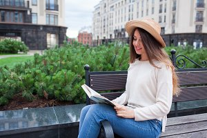 A young beautiful woman in an elegant hat sits on a bench in a new residential neighborhood and reads a paper book. She flips through the pages and smile. Urban background