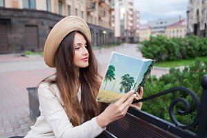 A young beautiful woman in an elegant hat sits on a bench in a new residential neighborhood and reads a paper book. She flips through the pages. Urban background