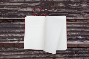 The red notebook lying on a wooden bench. The wind leafing through the blank pages
