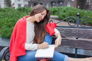 Attractive girl sitting on a bench with bare feet, covered with a red blanket, in the new residential area and writes his thoughts into a red notebook. The urban background