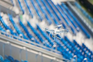 White quadcopter flies over the football stadium and shoots video. The drone on the background of blue seats at the stadium