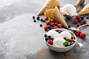 Vanilla ice cream scoops in a bowl with fresh berries
