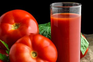 Organic tomato juice in glass and fresh tomatoes with green leaves on dark