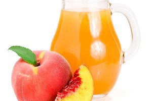 Peach juice in a glass jug isolated on white background