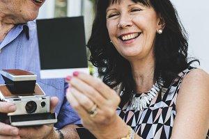 Senior couple taking instant photos