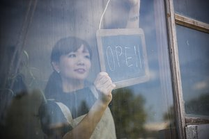 Woman putting open sign front shop